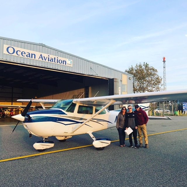 Students standing outside of Ocean Aviation by plane